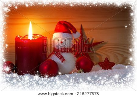 Christmas snowman with red scarf and santa claus hat , isolated on wood background.Advent candle and Snowman. Christmas background with snow frame.