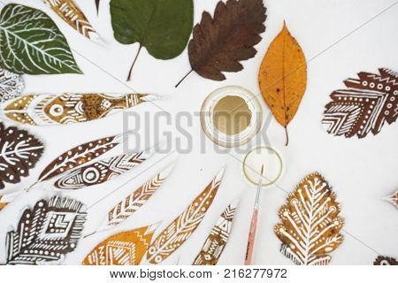 The process of painting on leaves. Many autumn dry leaves with ethnic patterns brush and a gouache can top view. Selective focus.