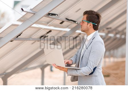 A solid man in a suit with a pencil behind his ear, holds a modern laptop in his hands and looks at the wiring harness for the solar panels installed on the roof. Outdoors