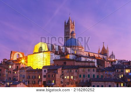 Beautiful view of Dome and campanile of Siena Cathedral, Duomo di Siena, and Old Town of medieval city of Siena during evening blue hour, Tuscany, Italy