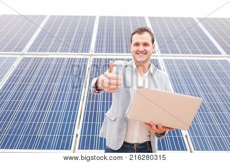 Happy man of European appearance standing against a background of solar panels, holding an open modern laptop in his hands, smiling and showing his index finger in front of him. Outdoors