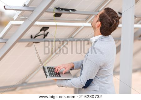 An adult man in a jacket checks the work of solar panels by connecting a modern laptop to a solar cell. Outdoors