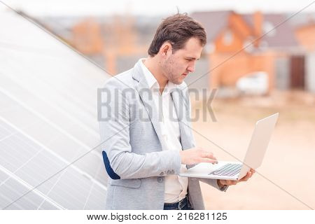 An employee of the solar station with a serious gaze holds an open modern laptop, standing next to the solar panel. Outdoors.