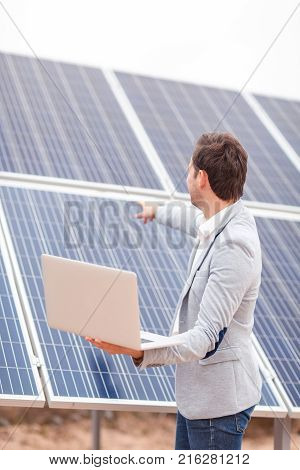 An adult man in a jacket holds an open modern laptop in his hands, and shows directional guidance on the panel of the solar battery. Outdoors .