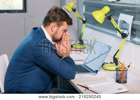 Frustrated brunette man in blue suit, office worker sitting at desk in office, looking at laptop with frustrated look. Indoors.