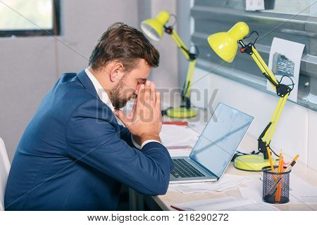 An unhappy man, an office worker sitting at the desk in the office, looks at the laptop with a frustrated gaze and clings to his face. Indoors.