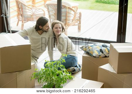 Happy couple just moved into modern house with terrace, smiling man and woman sitting bonding on the floor with cardboard boxes, starting living in new home, moving day concept, family relocation