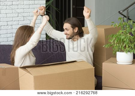 Young couple with cardboard boxes celebrating moving into new home, homeowners raising hands happy to relocate in own apartment sitting on sofa, independent man and woman enjoy start living together