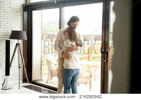 Young man and woman hugging standing at home interior, tender husband embracing wife gently, showing love and support, couple reconciliation concept, understanding in relationships, making up