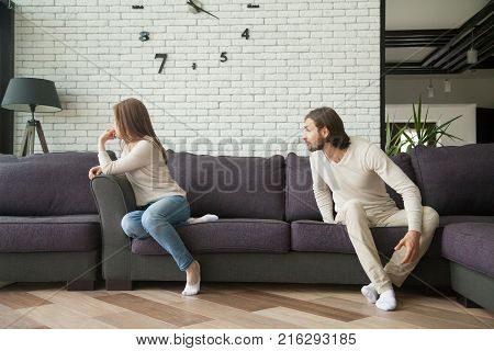 Young couple arguing sitting on sofa, man shouting at woman on couch in living room, offended wife not talking to husband, dissatisfied boyfriend blaming girlfriend, family problems, marital conflict