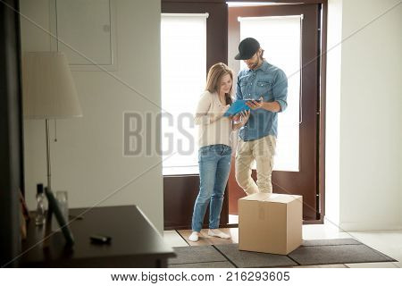 Young woman putting signature receiving cardboard box from courier at home, receiver singing document for accepting parcel, man delivering package to customer, door delivery service concept poster