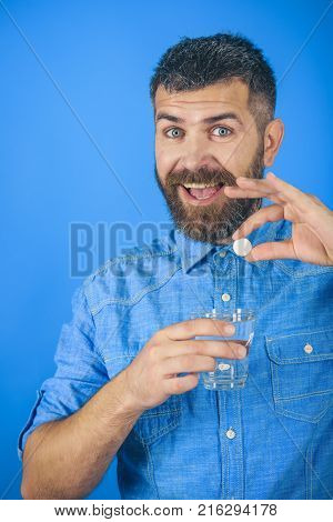 happy hipster drink pill with water. painkiller drug and antidepressant. Treatment hypnotic tablet. Health and medicine flu and cold. Man with beard hold water glass on blue background headache.
