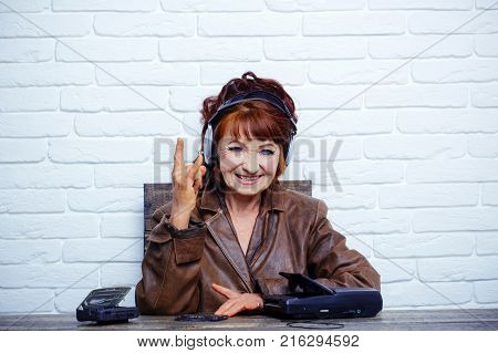 Spy and operator. Old woman with cassette recorder listen music in headphones. Old school music player radio. Audio book and new technology education. happy granny dj in headset with cassette player