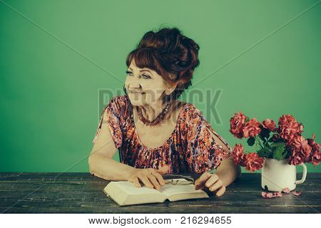 Old woman reading book with glasses at flowers. Pension and retirement old age. happy old lady or grandmother. Writer and poet granny read fairytale. Teacher or professor education teachers day.