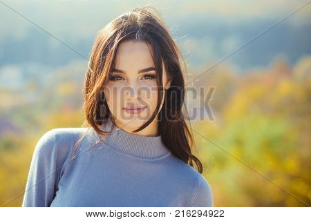 Girl with long brunette hair enjoy autumn nature. Woman face with makeup on sunny day. Skincare youth health. Cosmetics visage make up. Fashion beauty concept.
