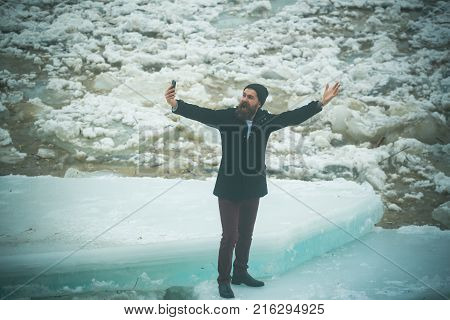 Man with beard make selfie photo at ice block. man with frozen hummock and mobile phone. Cold weather and ice age. Cracked ice background and guy in Christmas. Winter holiday and new technology.