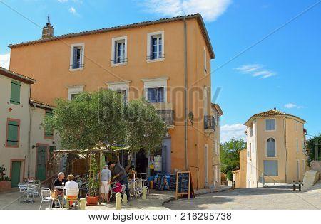 BADGES, LANGUEDOC - ROUSSILLON, FRANCE - SEPTEMBER 12, 2013: Diners at restaurants  in the village square Badges,
