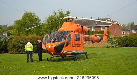 ST NEOTS, CAMBRIDGESHIRE, ENGLAND - APRIL 30, 2017:  Cambridgeshire  air ambulance Helicopter  landed in housing estate at St Neots  crew standing by.