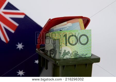 Australian dollars in a trash bin with the Australian flag in the background.
