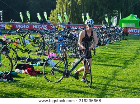 ST NEOTS, CAMBRIDGESHIRE, ENGLAND - SEPTEMBER 11, 2016: Triathlon competitor  just starting cycling stage of competition.