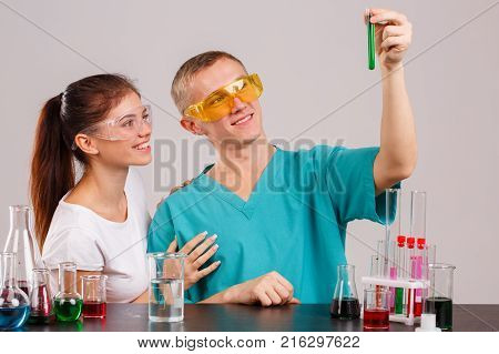 Two laboratory assistants in uniform and special glasses. The guy is holding a small glass flask with a green liquid in his hands and looking at it. Indoors laboratory. Isolation.