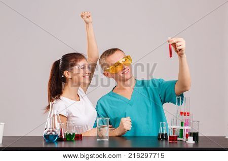 A pair of happy young laboratory assistants in uniform and special glasses are enjoying a successful experiment, holding a small glass flask with a red liquid. Indoors laboratory. Isolation.