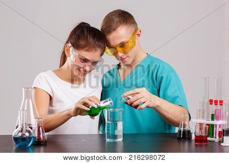 Two lab technicians in uniform and special glasses pour out the red and green liquid from two small glass flasks into an audible glass beaker with clear liquid. Indoors laboratory. Isolation.