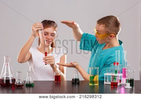 Two young laboratory assistants in special glasses and uniforms, the girl pours a red liquid from a measuring pipette into a glass flask, the guy shows his hands the size. Indoors laboratory. Isolation.