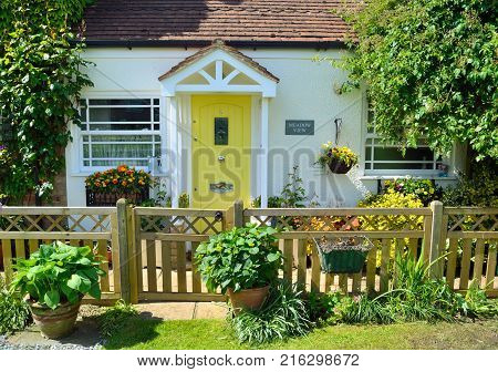 OFFORD DARCY, CAMBRIDGESHIRE, ENGLAND - MAY 22, 2017:  Cottage  with picket fence and Yellow door.