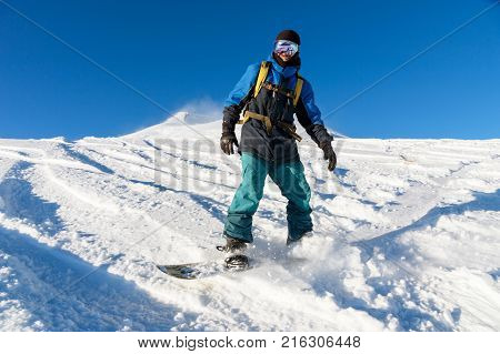 A freeboard snowboarder in a ski mask and a backpack skates over the snow-covered slope leaving behind a snow powder against the blue sky