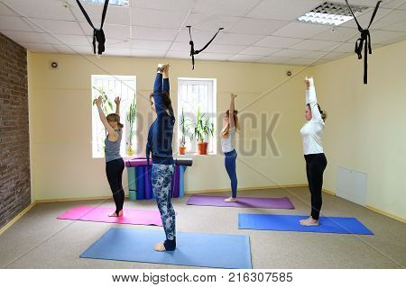 Group of four people performs basic exercises from yoga. European girls doing weight loss exercises. Concept of group sports, exercises to restore physical form.