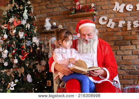 Inquisitive female child listens attentively to interesting story from book read by Santa Claus in cozy and spacious room decorated for New Years holidays