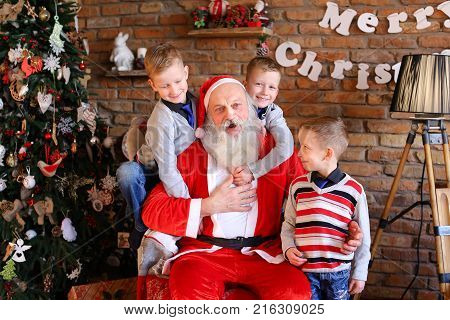 Happy male children and Christmas grandfather posing smiling at camera. boys cheerfully wiggle their hands Santa Claus shows gesture with thumb up,