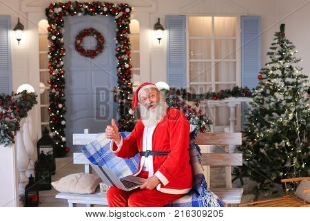 Cheerful Santa Claus making video call in cozy apartments. Gladden man in red costume satisfying with joyful ambience. Concept of communication with Father Christmas using modern gadget.