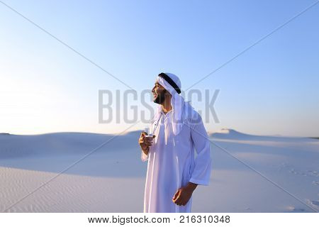 Stately Arab young man quenches thirst with glass of cool water and feels influx of strength and energy, smiles and looks to side, standing amidst endless sandy desert with pure white sand in open air on warm summer morning. Swarthy Muslim with short dark