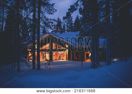 A Cozy Wooden Cabin Cottage Chalet House Covered In Snow Near Ski Resort In Winter With The Lights T