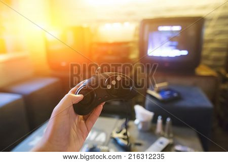 A young man holding game controller playing video games. Oldschool console. Gaming concept. Closeup shot.
