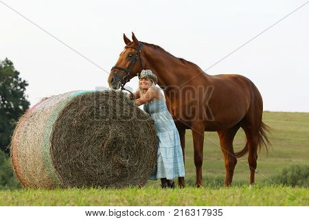 Romantic summer scene with woman and her horse on meadow