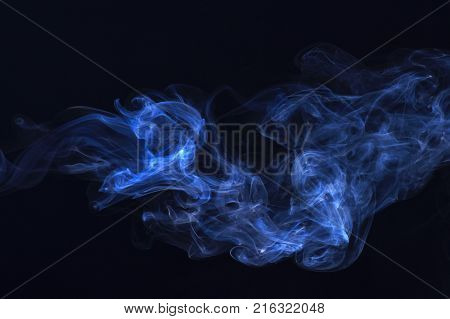 Spirit and ghost miracle. Smoking cloud backdrop. Blue ink in freeze motion powder splatted explosion. Blue smoke on black background. Abstract background with smoke.