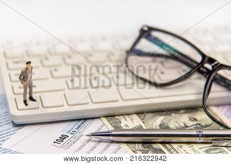 Miniature businessman calculating tax for income tax return for saving. Tax and Saving Concept
