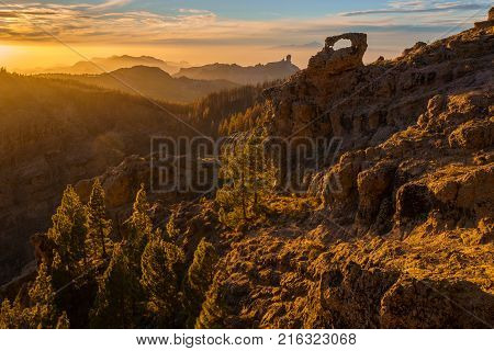 spectacular sunset over roque nublo mountain on Gran Canaria in the background visible volcano Teide on tenerife