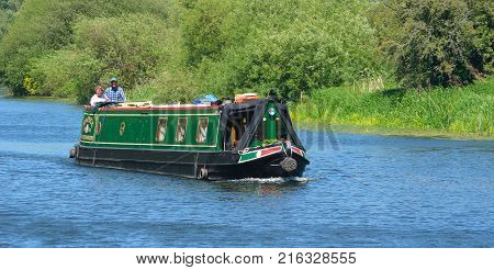 ST NEOTS, CAMBRIDGESHIRE, ENGLAND - MAY 26, 2017: Traditional Narrow Boat on the River Ouse  near St Neots Cambridgeshire.