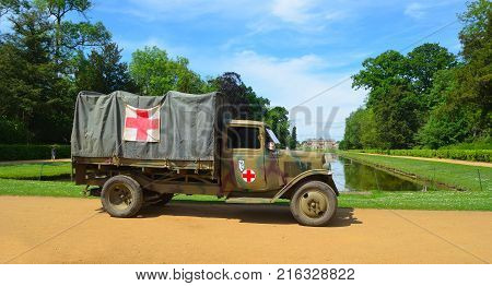 SILSOE, BEDFORDSHIRE, ENGLAND - MAY 28, 2017: Vintage Second World War truck with red cross signs  parked  with Wrest Park House in background