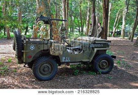 SILSOE, BEDFORDSHIRE, ENGLAND - MAY 28, 2017:  Second World War  Jeep with machine Gun parked in woods with men dressed in uniforms in background.