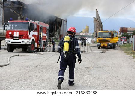 Fire disaster in a warehouse. Fire fighting in an industrial area. Fire trucks.