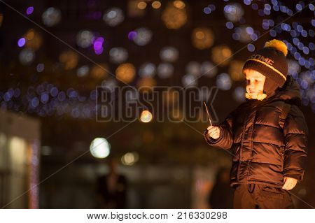 Little boy with burned down sparkler on blurred bokeh backgroundOutdoors photography. Boy is looking at sparkler in his hand.