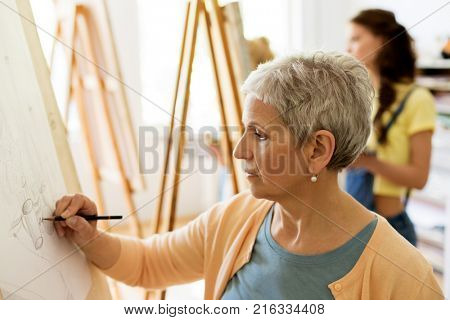 creativity, education and people concept - senior woman drawing on easel at art school studio