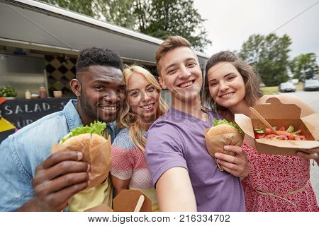 leisure, eating and people concept - happy friends with wok and burgers taking selfie at food truck