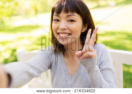 people and technology concept - happy smiling asian woman taking selfie at park and showing peace hand sign