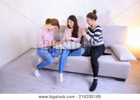 Lovely women spend time together and engaged in women's affairs. Two women help to get girlfriend to meet with guy, paint nails and lips, braid hair, chat and joke, sitting on soft gray sofa in bright room in evening. One European-looking girl with medium